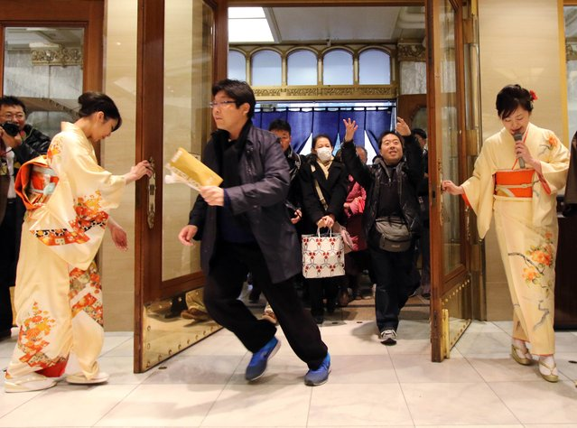 """Japanese shoppers rush into a Tokyo department store to buy """"lucky bags"""" containing items worth three times their price tag to celebrate a new year of business in Tokyo on January 2, 2015. Lucky bags are sold each year to celebrate the New Year, Japan's biggest holiday of the year. (Photo by Yoshikazu Tsuno/AFP Photo)"""