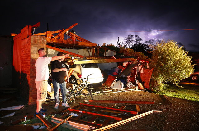 Derrek Grisham, left, points out neighborhood damage to storm chaser Travis Schafer after a tornado damaged his mother's house on Hyde Park Lane at Country Club Rd. in Cleburne, Texas,Wednesday night, May 15, 2013. Cleburne Mayor Scott Cain early Thursday declared a local disaster as schools canceled classes amid the destruction. (Photo by Tom Fox/AP Photo/The Dallas Morning News)