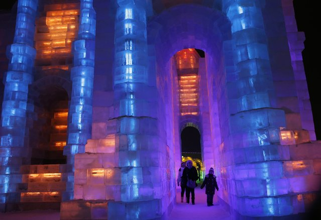 People visit ice sculptures illuminated by coloured lights during a trial operation ahead of the 31st Harbin International Ice and Snow Festival in the northern city of Harbin, Heilongjiang province, January 4, 2015. (Photo by Kim Kyung-Hoon/Reuters)