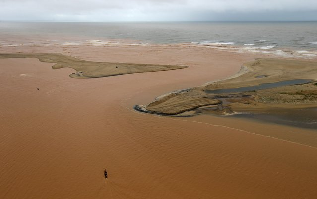 A boat is seen on the mouth of Rio Doce (Doce River), which was flooded with mud after a dam owned by Vale SA and BHP Billiton Ltd burst, as the river joins the sea on the coast of Espirito Santo in Regencia Village, Brazil, November 22, 2015. (Photo by Ricardo Moraes/Reuters)