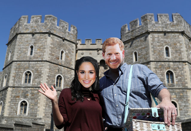 A couple wear Prince Harry and Meghan Markle face masks outside Windsor Castle, in Windsor, Britain, May 15, 2018. (Photo by Marko Djurica/Reuters)