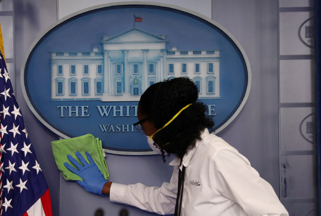 Workers clean the area around the podium before the daily coronavirus disease (COVID-19) outbreak task force briefing in the briefing room at the White House in Washington, U.S., April 13, 2020. (Photo by Leah Millis/Reuters)