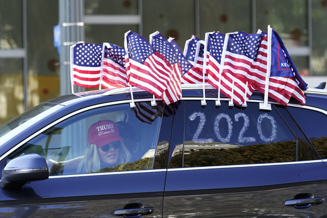 A protester joins a car caravan outside of City Hall Wednesday, January 6, 2021, in Los Angeles. Demonstrators, supporting President Donald Trump, are gathering in various parts of Southern California as Congress debates to affirm President-elect Joe Biden's electoral victory. (Photo by Marcio Jose Sanchez/AP Photo)