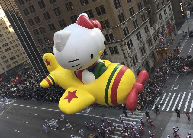 """The """"Hello Kitty"""" balloon proceeds high above spectators along 6th Ave during the 89th Macy's Thanksgiving Day Parade in the Manhattan borough of New York November 26, 2015. (Photo by Carlo Allegri/Reuters)"""
