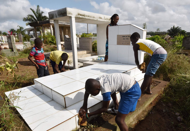 Children clean a grave on November 1, 2016 at the Williamsville cemetery in Abidjan, during the All Saints' Day. (Photo by Sia Kambou/AFP Photo)