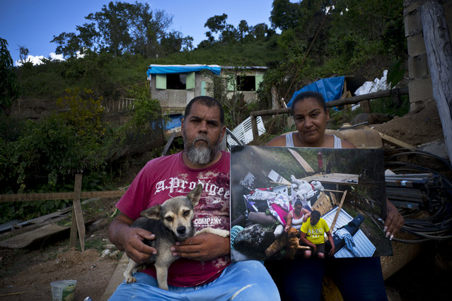 """William Fontan Quintero and his wife Yadira Sostre pose with a printed photo of them taken on September 30, 2017 when they sat amid the rubble of their home that was destroyed by Hurricane Maria, at the same spot where they rebuilt their home, behind, in the San Lorenzo neighborhood of Morovis, Puerto Rico, May 29, 2018. The couple says FEMA rejected their application for financial help but they received $8,000 from family to help them replace their belongings, which they invested in wood to build a small home, behind, where they live with their two children who are university students. The roof is plastic tarp while they wait for their FEMA application to be approved so they can finish rebuilding. """"We don't have time to build anything safe without help"""", said Quintero. (Photo by Ramon Espinosa/AP Photo)"""