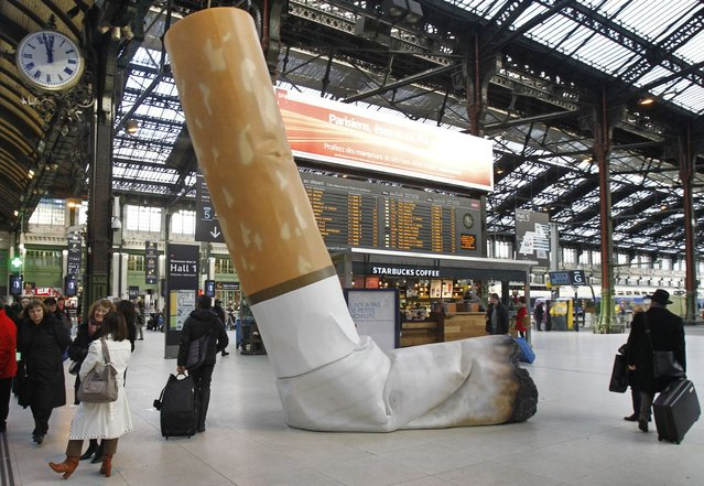 A symbolic cigarette butt is set up inside Gare de Lyon railway station, in Paris, Tuesday December 4, 2012, as part of a publicity campaign against rudeness, by Paris's public transport authority. The possibility of apparent rudeness is being counteracted by an advertising campaign as tourism companies and the Paris transport authority address concerns of tourists during the financial crisis. (Photo by Remy de la Mauviniere/AP Photo)