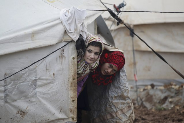Internally displaced girls look out from their tent inside Al-Karameh refugee camp beside the Syrian-Turkish border in Northern Idlib countryside January 10, 2015. A storm buffeted the Middle East with blizzards, rain and strong winds, keeping people at home across much of the region and raising concerns for Syrian refugees facing freezing temperatures in flimsy shelters. (Photo by Khalil Ashawi/Reuters)