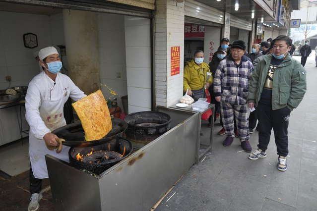 Residents wearing masks to help curb the spread of the coronavirus queue up at a popular food stall in Wuhan, China, Tuesday, January 26, 2021. The central Chinese city of Wuhan, where the coronavirus was first detected, has largely returned to normal but is on heightened alert against a resurgence as China battles outbreaks elsewhere in the country. (Photo by Ng Han Guan/AP Photo)
