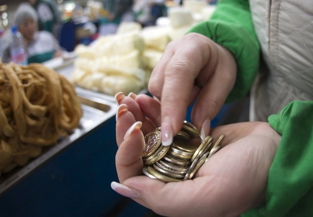 A saleswoman at the dairy department counts coins at the Green Bazaar in Almaty January 23, 2015. (Photo by Shamil Zhumatov/Reuters)
