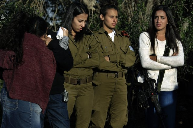 Friends and relatives of of Staff Sergeant Dor Chaim, mourn during his funeral in Moshav Shtulim, southern Israel, Thursday, January 29, 2015. Israeli Prime Minister Benjamin Netanyahu on Thursday said that Iran is to blame for a deadly flare-up along the Israeli-Lebanese border the previous day, the deadliest escalation in the disputed zone since the 2006 war between Hezbollah and Israel. (Photo by Tsafrir Abayov/AP Photo)