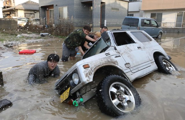 Residents try to upright a vehicle stuck in a flood hit area in Kurashiki, Okayama prefecture on July 9, 2018. Rescue workers, police and troops in Japan battled on July 9 to reach people feared trapped by devastating flooding and landslides after days of record rainfall killed at least 75 people. (Photo by AFP Photo/JIJI Press)