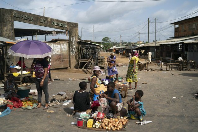 A woman sits next her goods to sale on a street market in Bonoua, in the outskirts of Abidjan, Ivory Coast, Friday, October 30, 2020. (Photo by Leo Correa/AP Photo)