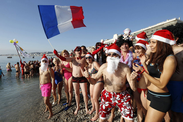 People wearing swimsuits, Christmas hats, and holding a French flag, attend the traditional Christmas on December 20, 2015 on the beach of the French riviera city of Nice, southeastern France. (Photo by Valery Hache/AFP Photo)