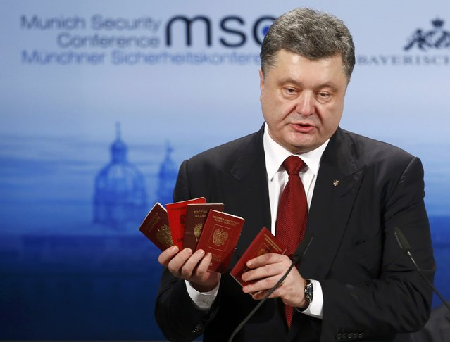 """Ukraine's President Petro Poroshenko holds Russian passports to prove the presence of Russian troops in Ukraine as he addresses during the 51st Munich Security Conference at the """"Bayerischer Hof"""" hotel in Munich February 7, 2015. (Photo by Michael Dalder/Reuters)"""