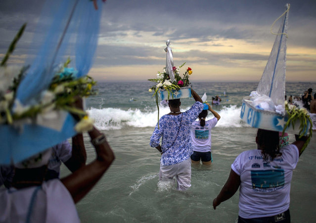 People participate in a parade paying tribute to Yemoja, (Iemanja, in Portuguese), female God of the sea, in Copacabana Beach, Rio de Janeiro, Brazil, 29 December 2015. Yemoja reaches more believers every year on 29 December, when tourists crowd Rio de Janeiro streets, in a parade passing by different places of the city. (Photo by Antonio Lacerda/EPA)