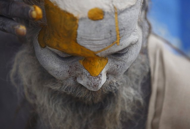 Hindu holy man, or sadhu, applies paint to his forehead at his ashram on the premises of Pashupatinath Temple in Kathmandu February 15, 2015. Hindu holy men from Nepal and India come to this temple to take part in the Maha Shivaratri festival. Celebrated by Hindu devotees all over the world, Shivaratri is dedicated to Lord Shiva. (Photo by Navesh Chitrakar/Reuters)