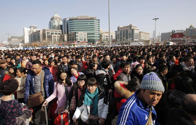 Passengers wait in a line to enter a platform at a railway station in Beijing February 16, 2015. (Photo by Kim Kyung-Hoon/Reuters)