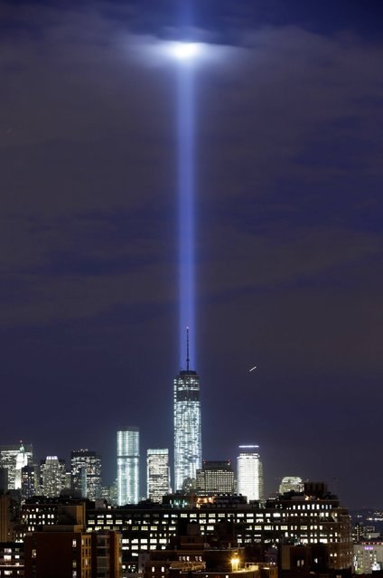 In this photo made with a long exposure, a test of the twin beams of the Tribute in Light intersect with still-under construction Tower One as they rise behind the building and above lower Manhattan, Monday, September 9, 2013, in New York. The memorial, sponsored by the Municipal Art Society, will light the sky on the evening of September 11, 2013, in honor of those who died in the September 11, 2001, terror attacks on the United States. (Photo by Kathy Willens/AP Photo)