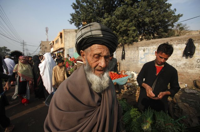 An elderly Afghan refugee man, who have residency a card which will expire on December 2015, walks along a market on the outskirts of Peshawar February 18, 2015. (Photo by Fayaz Aziz/Reuters)