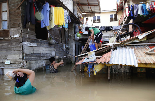 In this Monday, September 17, 2018, file photo, a couple wade through floodwaters to buy drinking water following flooding brought about by Typhoon Mangkhut which barreled into northeastern Philippines during the weekend and inundated low-lying areas in its 900-kilometer wide cloud band in Calumpit township, Bulacan province north of Manila, Philippines. A Philippine mayor says it's highly unlikely any of the 40 to 50 people who are feared buried in a mudslide set off by Typhoon Mangkhut can be found alive. (Photo by Bullit Marquez/AP Photo)