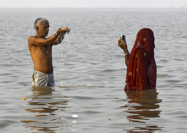 "A Hindu pilgrim uses a mobile phone to take pictures of her relative at the confluence of the river Ganges and the Bay of Bengal on the occasion of ""Makar Sankranti"" festival at Sagar Island, south of Kolkata, India, January 15, 2016. (Photo by Rupak De Chowdhuri/Reuters)"
