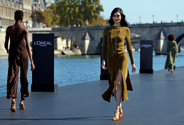 A model Ming Xi presents a creation on a giant catwalk installed on a barge on the Seine River during a public event organized by French cosmetics group L'Oreal as part of Paris Fashion Week, France, September 30, 2018. (Photo by Stephane Mahe/Reuters)