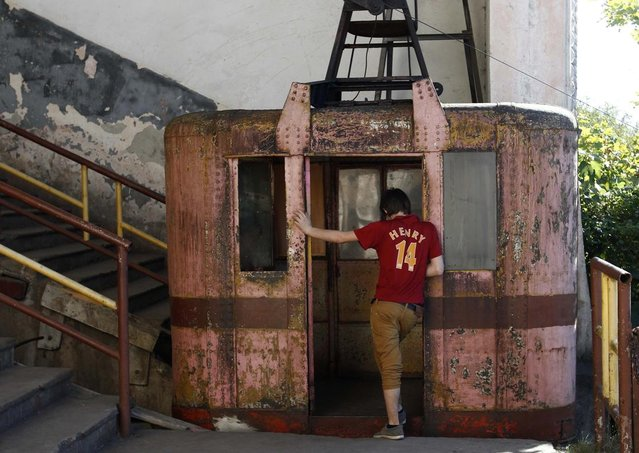 A boy stands at the door of a 60-year-old cable car in the town of Chiatura, some 220 km (136 miles) northwest of Tbilisi, September 12, 2013. (Photo by David Mdzinarishvili/Reuters)