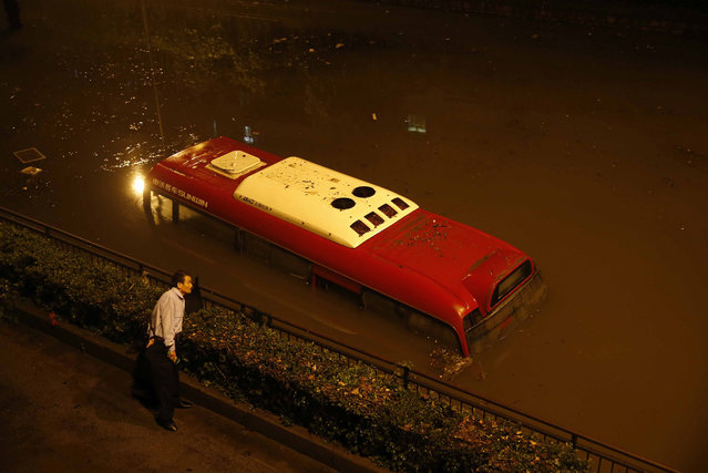 In this October 8, 2013. photo, a man looks at a passenger bus submerged in a flooded underpass in Songjiang district, Shanghai, China. Shanghai city officials closed more than 60 parks and the city zoo as residents waded through flood waters after heavy rains hit the financial hub in the aftermath of Typhoon Fitow. (Photo by AP Photo)