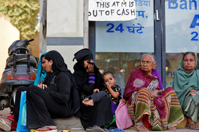 Women sit outside a bank as they wait for their turn to deposit or withdraw cash in Ahmedabad, India, November 29, 2016. (Photo by Amit Dave/Reuters)