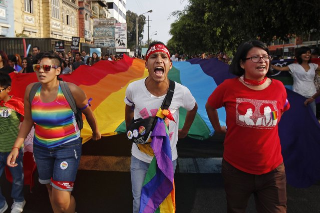 Members of gay and lesbian organizations hold a Gay Pride flag as they march in support of the Civil Union project law in Lima, March 7, 2015.  REUTERS/Enrique Castro-Mendivil (PERU - Tags: POLITICS SOCIETY)