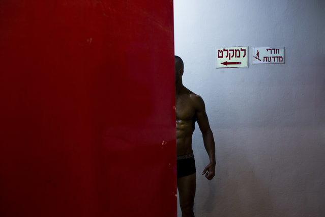 In this Thursday, October 18, 2018 photo, a contestant has his body painted backstage  during the National Amateur Body Builders' Association competition in Tel Aviv, Israel. In the run up to the flex-off, men and women, young and old, Jews and Arabs from around the country worked together to get ready for the big show. (Photo by Oded Balilty/AP Photo)