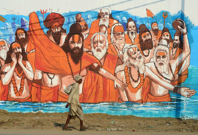 An Indian man walks past a mural painting at Naini central jail as part of an ongoing project 'Paint my City' for the upcoming Kumbh Mela festival, in Allahabad on October 29, 2018. (Photo by Sanjay Kanojia/AFP Photo)
