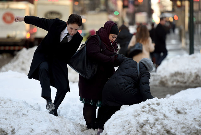 People try to navigate a snowbank in the middle of Park Avenue January 25, 2016 as New Yorkers return to work after the city was hit with a record-setting snowfall. (Photo by Timothy A. Clary/AFP Photo)