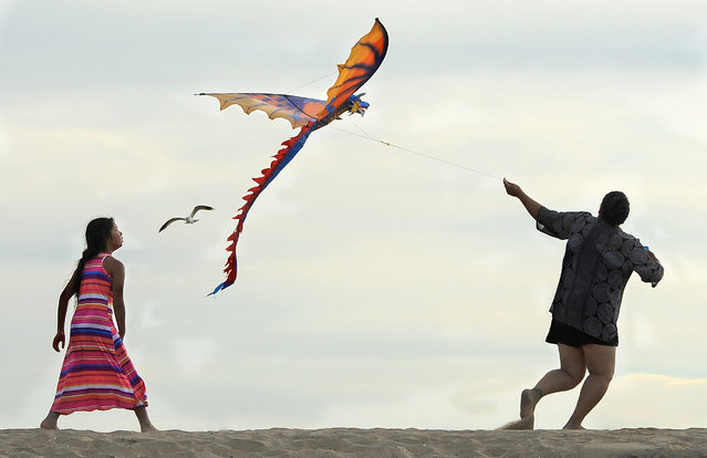 Two people fly a kite in Seal Beach, Calif., on a breezy Sunday, March 15, 2015. The expected heat was diminished by cloud cover. (Photo by Ana Venegas/AP Photo/The Orange County Register)