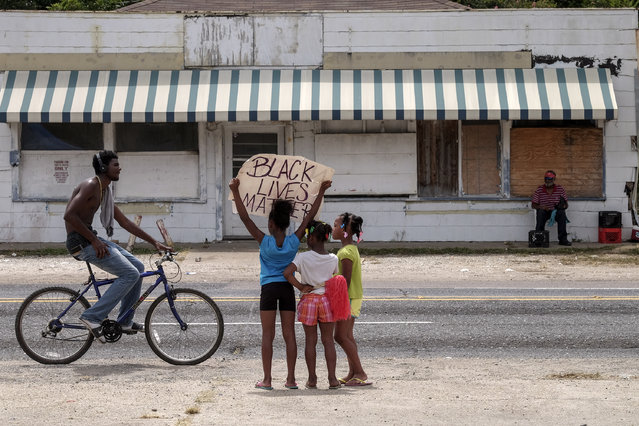 Dakeria Anderson, 9, protests with the help of her sisters D'liyah, 6, and D'anyriah, 8, across the street from the Triple S market where Alton Sterling wash shot and killed in Baton Rouge, LA, on July 11, 2016. The girls father, Dewayne Anderson said that he had been protesting since the beginning and the girls wanted to know what it was all about. The other side of the sign reads: no justice no peace. (Photo by Bonnie Jo Mount/The Washington Post)