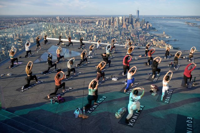 """Yoga practitioners attend a class on the Edge Observation Deck, billed as the """"highest outdoor sky deck in the Western Hemisphere"""" at 1,131 feet (345 meters), and overlooking the Manhattan skyline, in New York, on June 17, 2021. Pandemic restrictions have been gradually lifted in the US with just over 52 percent of the US population, or 174 million people, having received at least one dose, according to health officials. On June 14, New York city announced that 64.8 percent of adults had received at least one dose of the Covid-19 vaccine. (Photo by Ed Jones/AFP Photo)"""