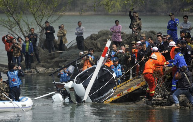 Rescuers pull the wreckage of a small helicopter out of a lake in Hefei, Anhui province March 22, 2015. The pilot remained missing and the sole passenger was injured after the two-seated Ukraine-made helicopter fell into the lake on Friday night during an unregistered flight, local media reported. (Photo by Reuters/Stringer)