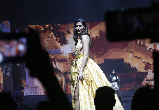 """One of the beauty queens from 35 countries displays a creation by Thai Silk during the opening ceremony of the first International Thai Silk Fashion Week 2018 in Bangkok, Thailand, 01 December 2018. The International Thai Silk Fashion Week 2018 as part of the 8th Celebration of Silk under the theme """"Thai Silk Road to the World"""", to showcase modern and traditional Thai silk and design from more than 50 international fashion designers and top Thai designers, will held from 01 to 09 December 2018. (Photo by Narong Sangnak/AFP Photo)"""