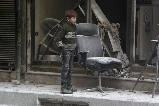A boy inspects damage after airstrikes by pro-Syrian government forces in the rebel held Al-Shaar neighbourhood of Aleppo, Syria February 4, 2016. (Photo by Abdalrhman Ismail/Reuters)