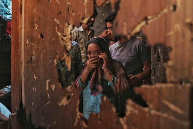 A kashmiri women reacts as she looks inside the house where suspected rebels had taken refuge is seen through a hole created by a mortar shell fired by government forces during a gunfight, in Srinagar, Indian-controlled Kashmir, on Friday, July 16, 2021. Two suspected rebels were killed in a gunfight in in the disputed region's main city on Friday, officials said, as violence increased in recent weeks. (Photo by Muhammad Manan/Pacific Press/Rex Features/Shutterstock)
