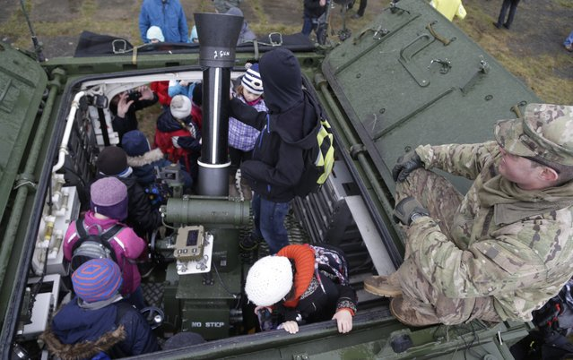 A US army soldier shows a stryker armored vehicle to children during a stop of their convoy in Prague, Czech Republic, Tuesday, March 31, 2015. (Photo by Petr David Josek/AP Photo)
