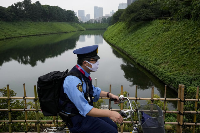 A police officer rides his bicycle along Imperial Palace Sunday, July 11, 2021, in Tokyo. The fourth state of emergency would go in effect on Monday and last through Aug. 22, despite the opening ceremony of Tokyo Olympics will be held in less than two weeks. (Photo by Kiichiro Sato/AP Photo)
