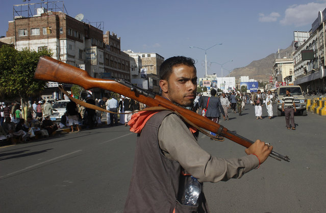 A Houthi Shiite rebel carries his weapon as he joins others to protest against Saudi-led airstrikes, during a rally in Sanaa, Yemen, Wednesday, April 1, 2015. Saudi-led coalition warplanes bombed Shiite rebel positions in both north and south Yemen early Wednesday, setting off explosions and drawing return fire from anti-aircraft guns. (Photo by Hani Mohammed/AP Photo)