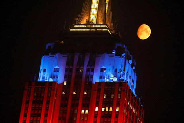 The moon, appearing orange due to smoke haze from forest fires, passes the Empire State Building in Manhattan, New York City, New York, U.S., July 20, 2021. (Photo by Andrew Kelly/Reuters)