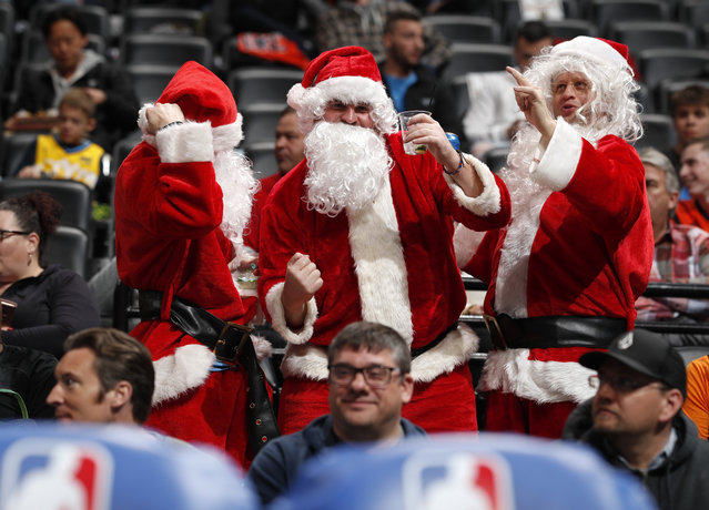 Fans dressed as Santa Claus dance behind the Oklahoma City Thunder bench in the first half of an NBA basketball game against the Denver Nuggets Friday, December 14, 2018, in Denver. (Photo by David Zalubowsk/AP Photoi)