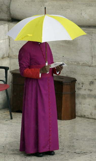 A Bishop stands under a umbrella in St. Peter's square before Pope Francis leads the Easter mass at the Vatican April 5, 2015. (Photo by Max Rossi/Reuters)