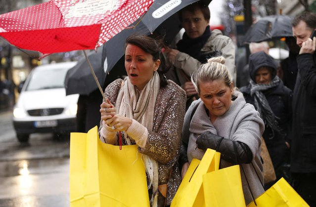 Shoppers walk in wet and windy weather on Oxford Street in central London December 23, 2013. (Photo by Olivia Harris/Reuters)