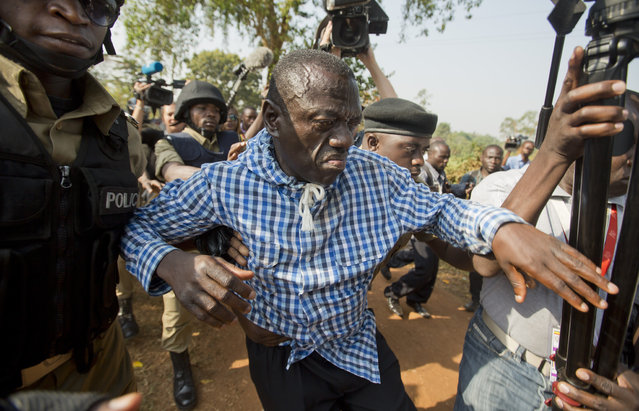 Uganda's main opposition leader Kizza Besigye, center, is arrested by police and thrown into the back of a blacked-out police van which whisked him away and was later seen at a rural police station, outside his home in Kasangati, Uganda Monday, February 22, 2016. Besigye was arrested again Monday as he tried to leave his home, in which he had already been placed under house arrest, as he attempted to visit the election commission's headquarters in Kampala to get detailed copies of the results from the country's presidential election. (Photo by Ben Curtis/AP Photo)