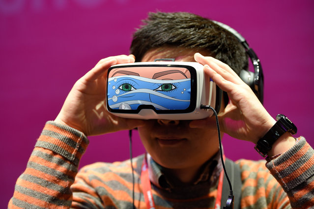"""A boy tests the """"Oculus VR"""" virtual device, at the stand of Deutsche Telekom during the Mobile World Congress in Barcelona on February 22, 2016, during the first day of the world's biggest mobile fair that runs to February 25. (Photo by Lluis Gene/AFP Photo)"""